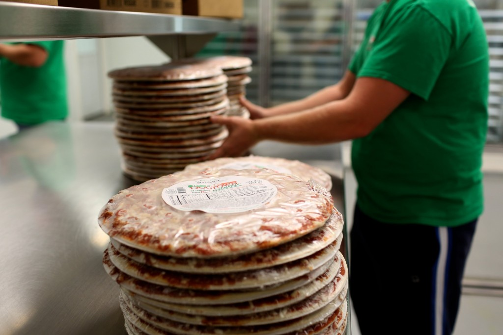 an employee wraps a frozen pizza.